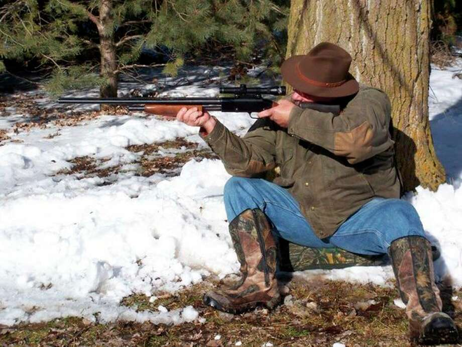 Above, the writer is doing pre-turkey season shooting practice by switch-hitting(being right handed, he is making sure to be able to shoot left-handed whenrequired). The Mossberg 20-gauge pump is fitted with a tight 'turkey' choke andtopped by a low power scope for precise shot placement. At left, the writer loves spring turkey hunting in Michiganand considers the wild turkey a conservation success storynationwide. (Photos courtesy of Tom Lounsbury/Hearst Michigan)