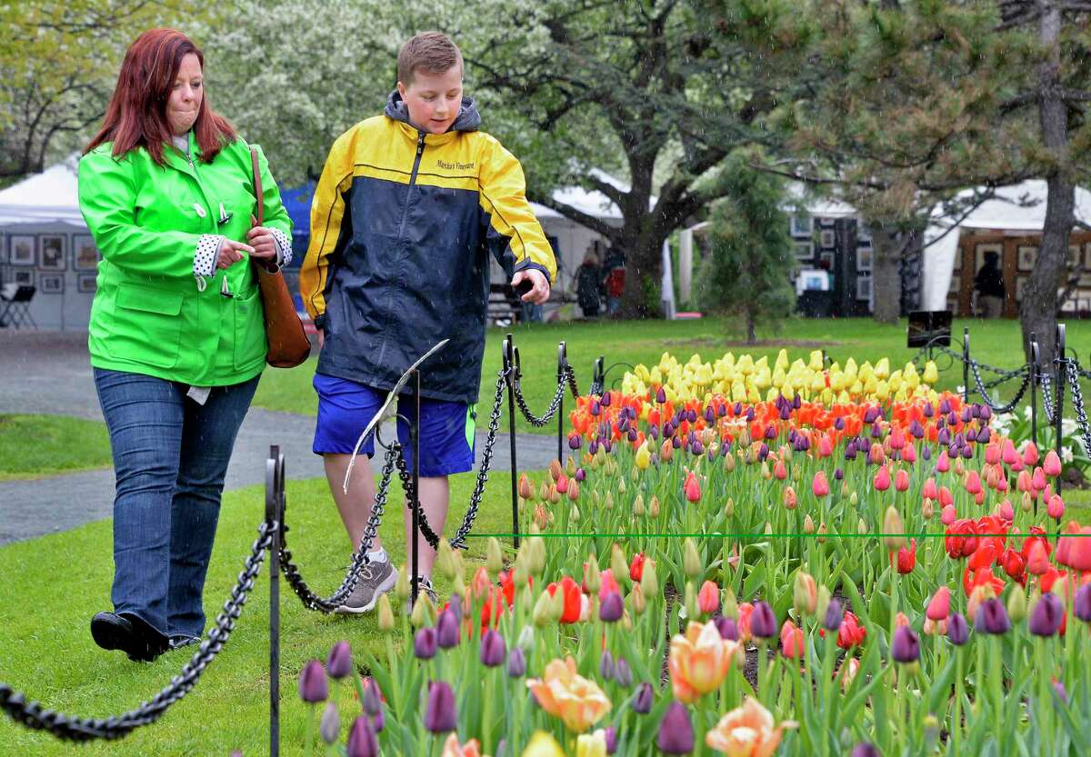 Jennifer Eslick, left, of Colonie is escorted through the tulip gardens by her son Noah, 11, during the 70th Annual Tulip Festival in Washington Park Saturday May 12, 2018 in Albany, NY. (John Carl D'Annibale/Times Union)