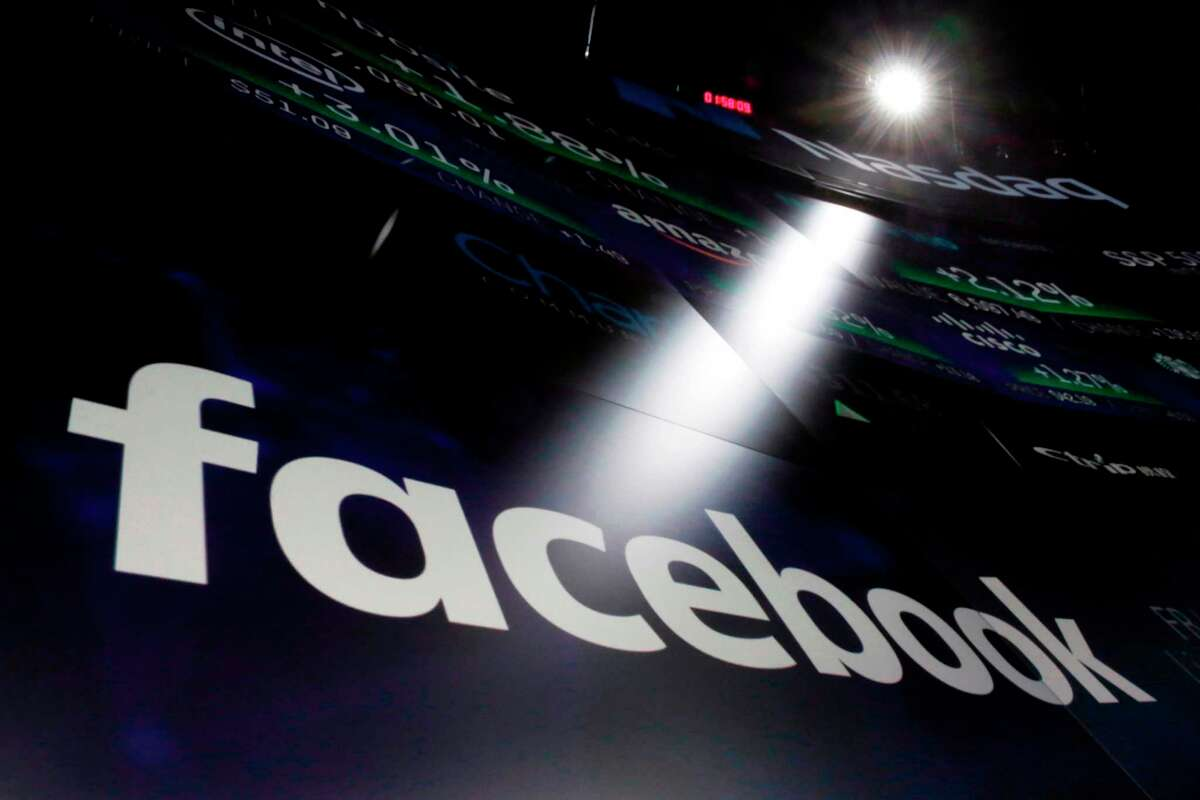 FILE- In this March 29, 2018, file photo, the logo for Facebook appears on screens at the Nasdaq MarketSite in New York's Times Square. Facebook is facing housing discrimination charges from the U.S. Department of Housing and Urban Development, which says its targeted advertising platform violates the Fair Housing Act. HUD claims Facebook's ad platform was