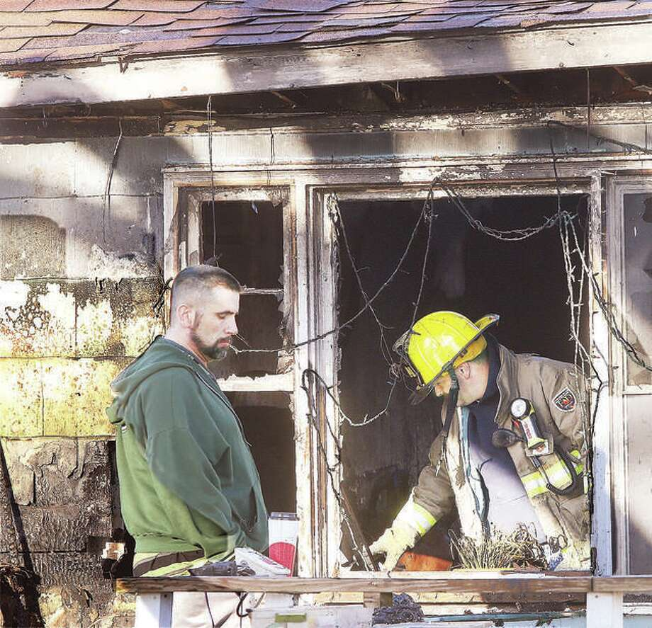 A firefighter examines the interior of the gutted house Wednesday. Firefighters were on the scene for over four hours.