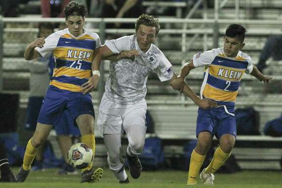 College Park midfielder James Ross-Kirov (8) fights for a ball between Klein midfielders Carlos Casolari (25) and Sammy Narvaez (2) during the first period of a District 15-6A high school soccer match at Klein High School, Friday, March 22, 2019, in Spring.