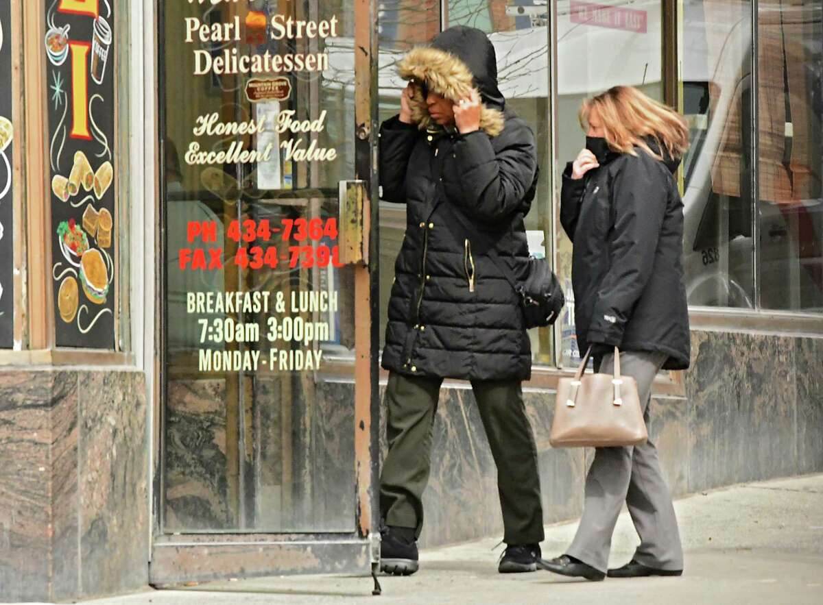Pedestrians shield their faces from a cold wind while they duck into a restaurant on South Pearl St. on Thursday, March 28, 2019 in Albany, N.Y. Winds will also be high Sunday, Jan. 12, 2020. (Lori Van Buren/Times Union)