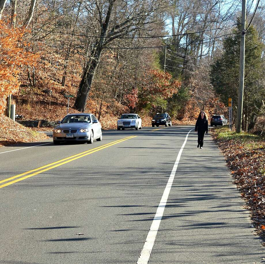 A pedesdtrian navigates a sidewalk-less stretch of Imperial Avenue by walking in the bike lane. Photo: Jarret Liotta / For Hearst Connecticut Media / Westport News