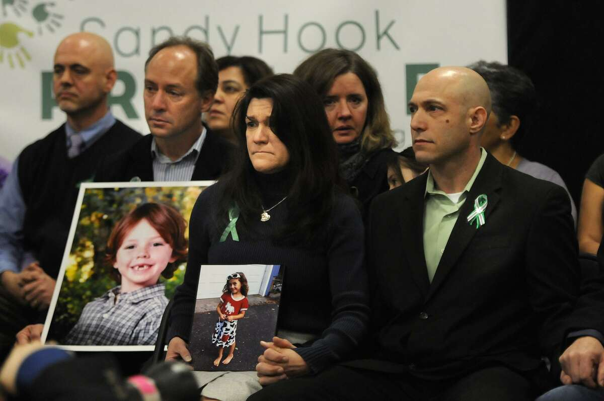 Jeremy Richman, right, during a press conference in January 2013 beside his wife Jennifer Hensel, center, holding a photo of their daughter Avielle, who was killed in the Dec. 14, 2012 Sandy Hook Elementary School shooting. Jeremy Richman was found dead early Monday at Edmond Town Hall in Newtown from an apparent suicide, police said.