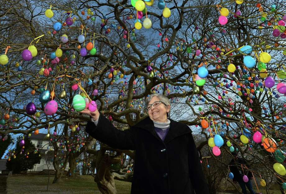 Norwalk resident Jalna Jaeger in the front yard of her East Avenue home Thursday in Norwalk. In the weeks leading up to Easter, Jaeger has hung plastic easter eggs from the limbs of a tree in her front yard for more than a decade.  A recent Facebook post about the tree got more than 1,000 likes from community members. Photo: Erik Trautmann / Hearst Connecticut Media / Norwalk Hour