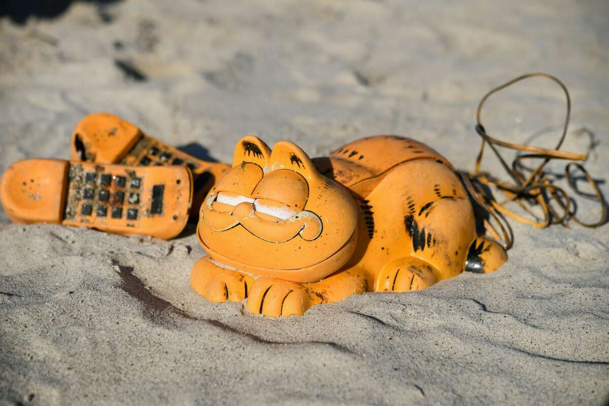 Spare parts of plastic 'Garfield' phones are displayed on the beach on March 28, 2019 in Plouarzel, western France, after being collected from a sea cave by environmental activists.