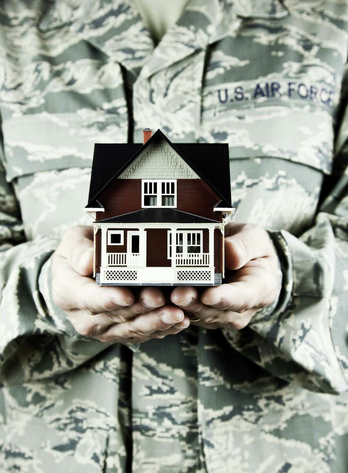 US soldier holding tiny home. (Getty Images)