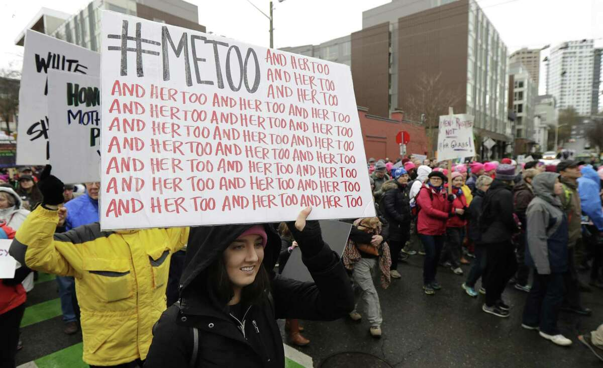 FILE - In this Saturday, Jan. 20, 2018 file photo, a marcher carries a sign with the Twitter hashtag #MeToo used by people speaking out against sexual harassment as she takes part in a Women's March in Seattle, on the anniversary of President Donald Trump's inauguration. A group of prominent U.S. foundations is launching a new fund aimed at combating sexual violence and harassment in the workplace. Organizers tell The Associated Press the fund was launched Thursday, March 14, 2019, and plans to direct most of its grants to programs led by and benefiting low-income workers, migrants and women of color. The 11 partners so far include the Ford Foundation, the Open Society Foundations, the Conrad Hilton Foundation and the NoVo Foundation. (AP Photo/Ted S. Warren)
