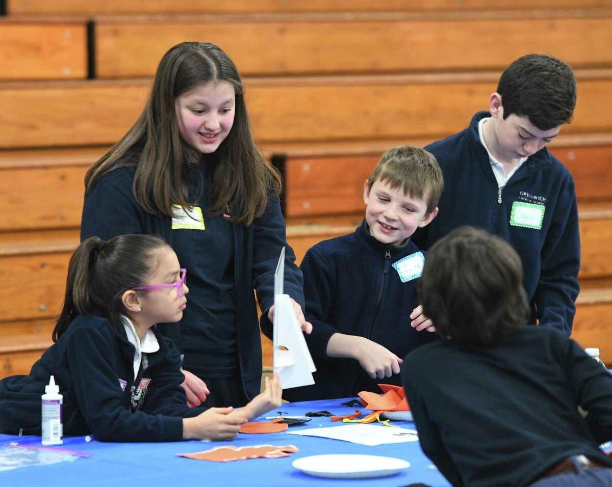 From left, second-garder Mia Jaramillo, seventh-grader Julia Marchetti, second-grader Henry Laufenberg, and seventh-grader Corey Guilfoyle work together on a project to benefit Norwalk nonprofit Malta House during the first annual Together in Kindness service day at Greenwich Catholic School in Greenwich, Conn. Thursday, March 28, 2019.