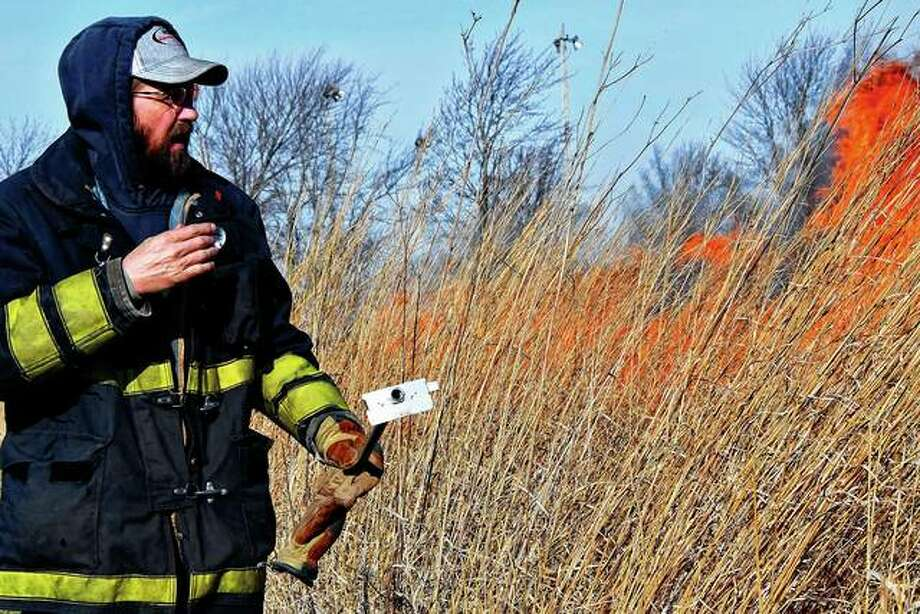 Virginia firefighter Chris Tracy checks on the fire Wednesday at a controlled burn at Rexroat Prairie. Such burns are important to prairie plants and can add vital nutrients.