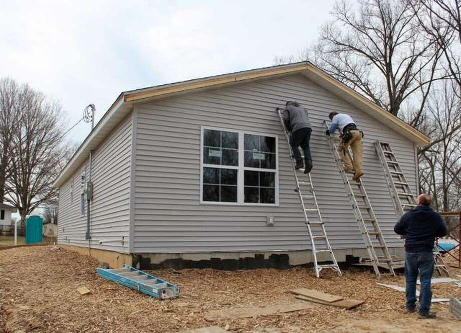 Volunteers take advantage of the weather Saturday by installing siding on two sides of the Habitat for Humanity house, located on Klein Avenue in Edwardsville. Photo: For The Intelligencer