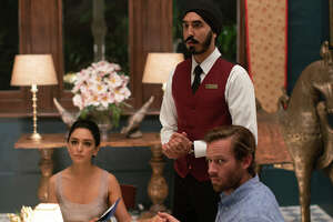 """This image released by Bleecker Street shows Nazanin Boniadi, from left, Dev Patel and Armie Hammer in a scene from """"Hotel Mumbai."""" (Mark Rogers/Bleecker Street via AP)"""