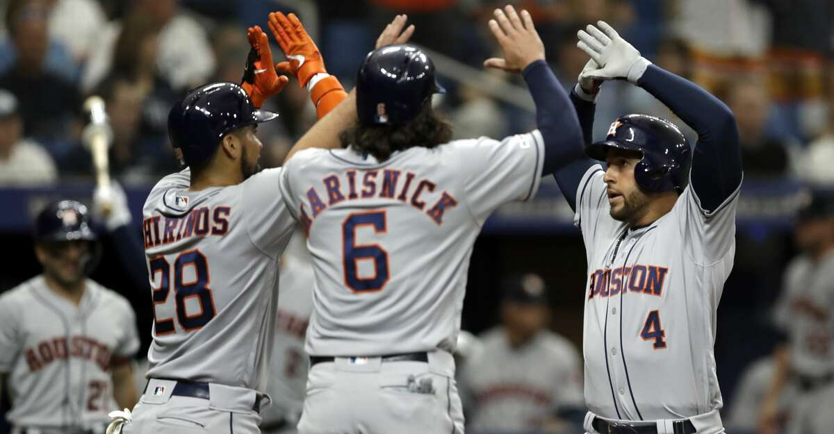 Houston Astros' George Springer (4) celebrates with Robinson Chirinos (28) and Jake Marisnick (6) after Springer hit a three-run home run off Tampa Bay Rays starting pitcher Blake Snell during the third inning of a baseball game Thursday, March 28, 2019, in St. Petersburg, Fla. (AP Photo/Chris O'Meara)