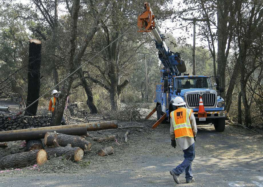 FILE - In this Oct. 18, 2017 file photo, a Pacific Gas & Electric crew works on replacing poles destroyed by wildfires in Glen Ellen. Photo: Ben Margot, Associated Press