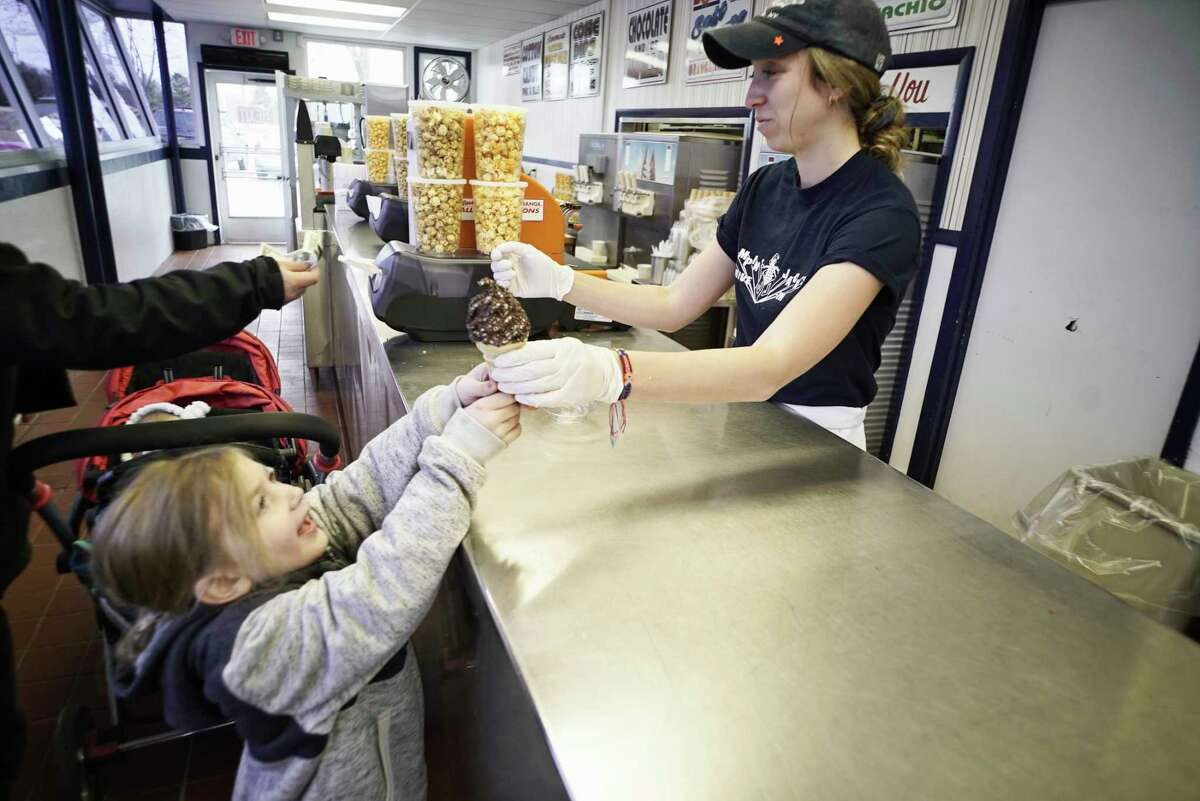 Amanda Chlopecki, 4, of Scotia reaches up to get her ice cream cone from Myah Hughes during opening day for Jumpin' Jack's on Thursday, March 28, 2019, in Scotia, N.Y. (Paul Buckowski/Times Union)