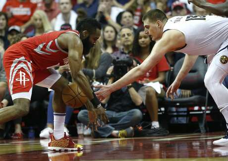 Houston Rockets guard James Harden (13) knocks the ball away from Denver Nuggets center Nikola Jokic (15) during the first half of an NBA basketball game at Toyota Center on Thursday, March 28, 2019, in Houston.