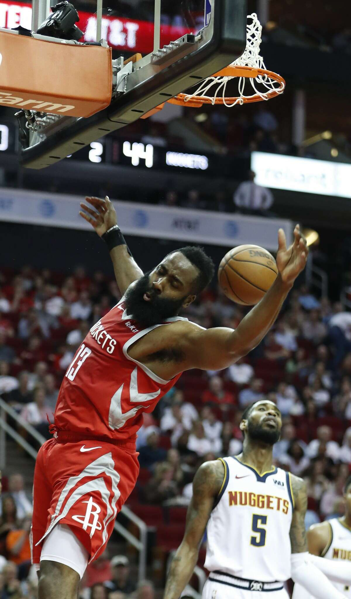 Houston Rockets guard James Harden (13) scores past Denver Nuggets guard Will Barton (5) during the first half of an NBA basketball game at Toyota Center on Thursday, March 28, 2019, in Houston.