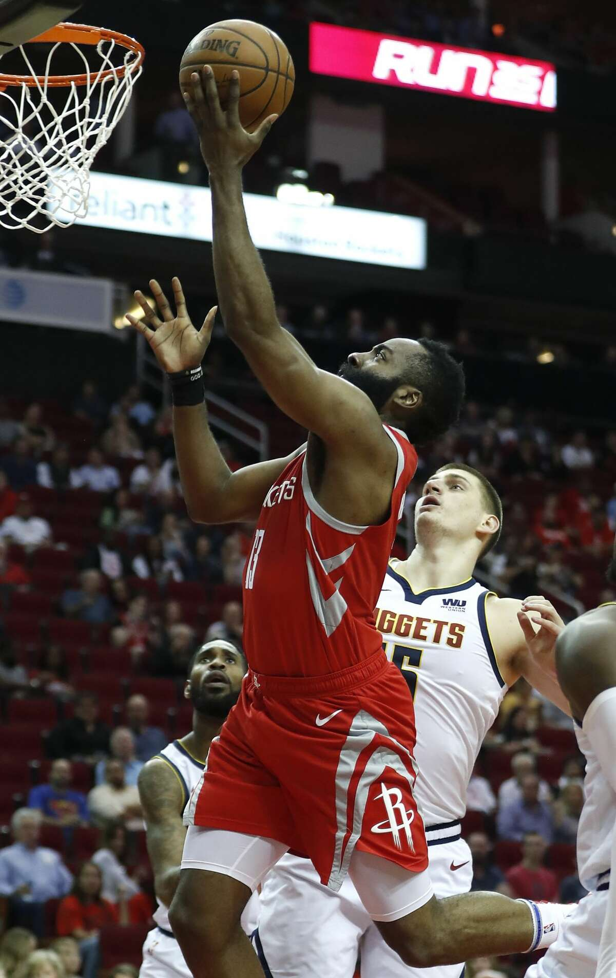 Houston Rockets guard James Harden (13) drives in for a layup past Denver Nuggets center Nikola Jokic (15) during the first half of an NBA basketball game at Toyota Center on Thursday, March 28, 2019, in Houston.