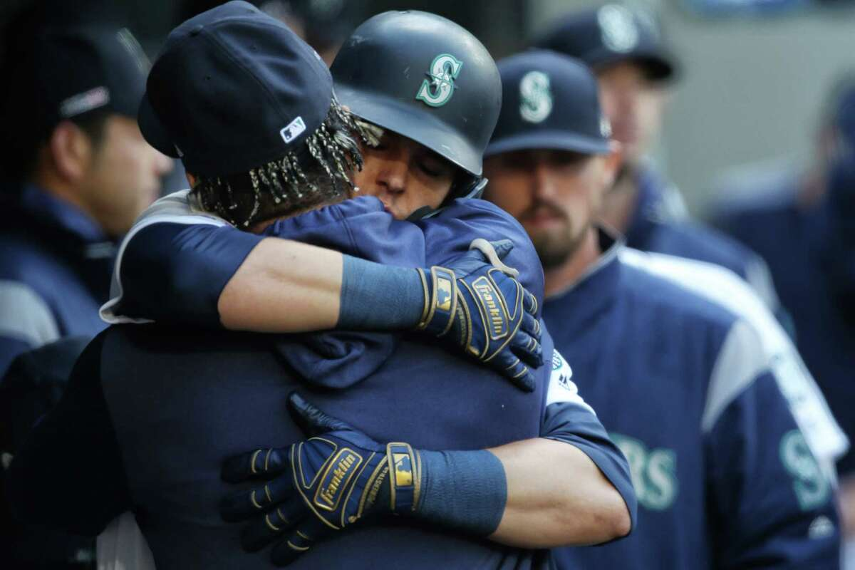 Seattle's Ryon Healy hugs Felix Hernandez after scoring a home run during the Seattle Mariner's home-opener against the Boston Red Sox at the newly renamed T-Mobile Park, Thursday, March, 28, 2019.