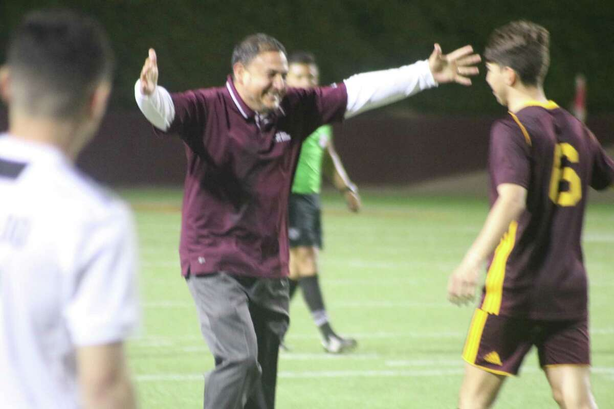 Deer Park head coach Jerry Hurtado prepares to give Alfonso Caballero a bear hug following the emotional bi-district championship win Thursday night.