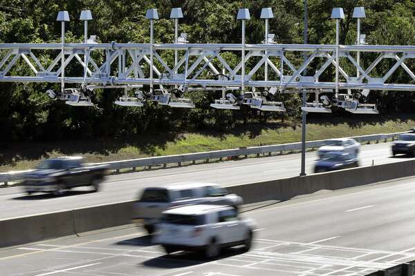 In a 2016 file photo, cars passed under the toll sensor gantries hanging over the Massachusetts Turnpike. Democrats in Connecticut are divided over a plan for tolls.