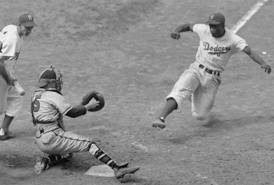 This Aug. 22, 1948 file photo shows Brooklyn Dodgers Jackie Robinson, right, stealing home plate as Boston Braves' catcher Bill Salkeld is thrown off-balance on the throw to the plate during the fifth inning at Ebbets Field in New York. Photo: File Photo / Stratford Booster Club