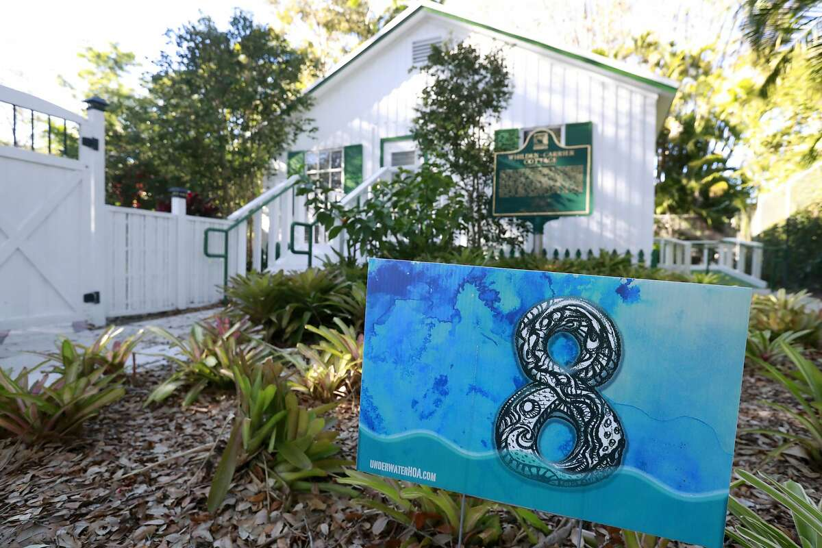 In this Wednesday, Feb. 6, 2019 photo, a yard sign stating that the area is eight feet above sea level is shown in front of artist Xavier Cortada's studio in Pinecrest, Fla. Cortada created an