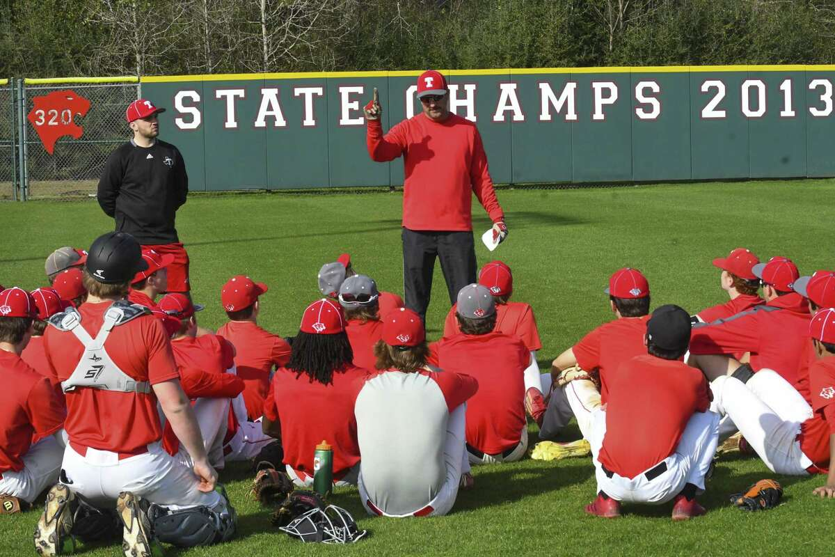 Doug Rush, head coach of the Tomball Cougars, talks baseball strategy with his team.