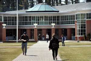 Students walk past the Carl Hansen Student Center at Quinnipiac University in Hamden on March 28, 2019.