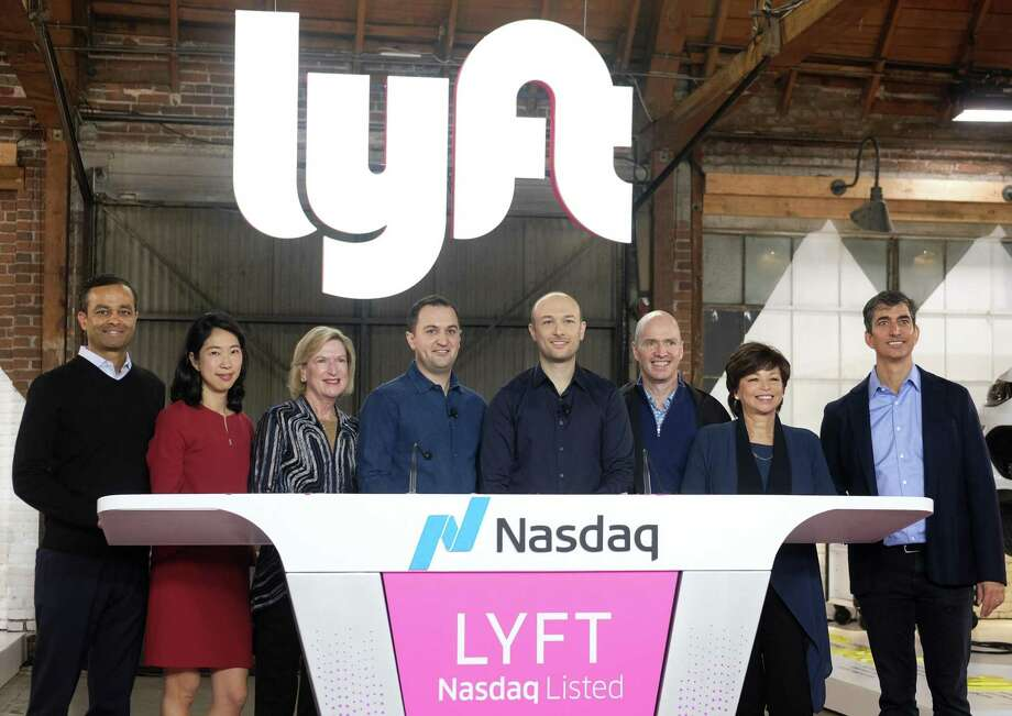 """Lyft co-founder, John Zimmer, fourth from left, and Logan Green, fourth from right, pose with the Lyft Board of Directors after they rang a ceremonial opening bell in Los Angeles, Friday, March 29, 2019. On Friday the San Francisco company's stock will begin trading on the Nasdaq exchange under the ticker symbol """"LYFT."""" (AP Photo/Ringo H.W. Chiu) Photo: Ringo H.W. Chiu / Associated Press / Copyright 2019 Associated Press. All rights reserved."""