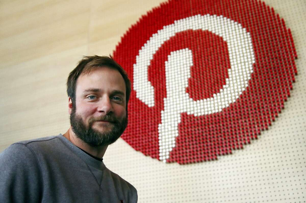FILE - In this Oct. 11, 2018, file photo, Evan Sharp, Pinterest co-founder and chief product officer, poses for a photo, standing beside a wall of pegs symbolizing the company logo at Pinterest headquarters in San Francisco. Pinterest is pinning its future on Wall Street, with the digital scrapbooking site on Friday, March 22, 2019, filing for an initial public offering of stock. (AP Photo/Ben Margot, File)