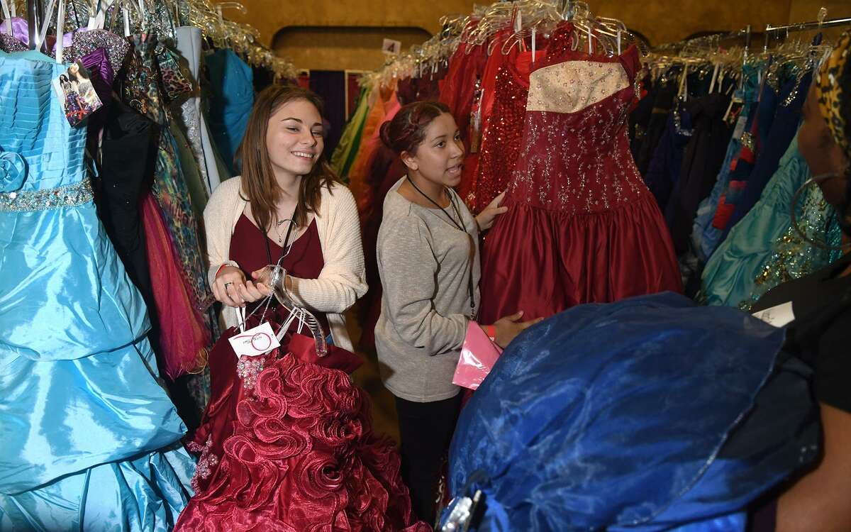 Savanah Baugh, 16, left, and Unique Trim, 16, both sophomores at La Porte High School, browse racks of dresses during day two of Boutique Day as part of the Giving Gown Foundation prom dress giveaway held at Bammel Church of Christ in Houston on March 28, 2019.