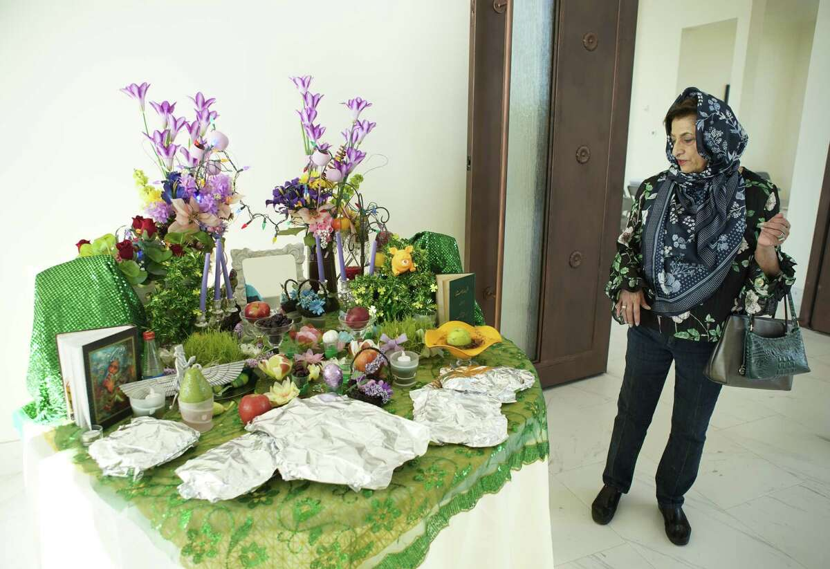 Aban Rustomji, the unofficial historian of Houston Zoroastrians, admires an Iranian display for Nowruz, the holiday that celebrates the spring equinox.