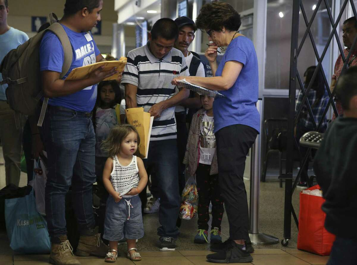 Two-year-old Juliet Giron, waits as her father, Brian Giron, 24, is helped by Interfaith Welcome Coalition volunteer Carolina Barrera at the Greyhound Bus station in San Antonio, Thursday, July 26, 2018. The Honduran family was released earlier today in McAllen. They were kept together during their ICE detention.