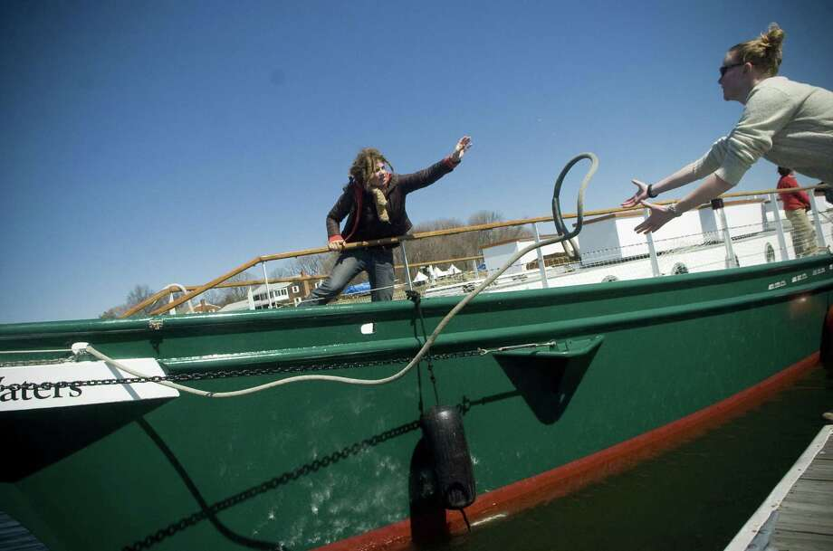 Emilee Monson, left, tosses a bow-line to crewmate Kat Murphy, after the schooner SoundWaters was put into the water at the Norwalk Cove Marina in Stamford, Conn. on Tuesday, March 31, 2009. Photo: CHRIS PREOVOLOS / ST