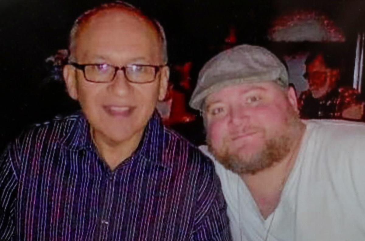 A photograph of Ed Gomez and his son, Jeremy Sweet-Gomez, in the father's Dallas law office.