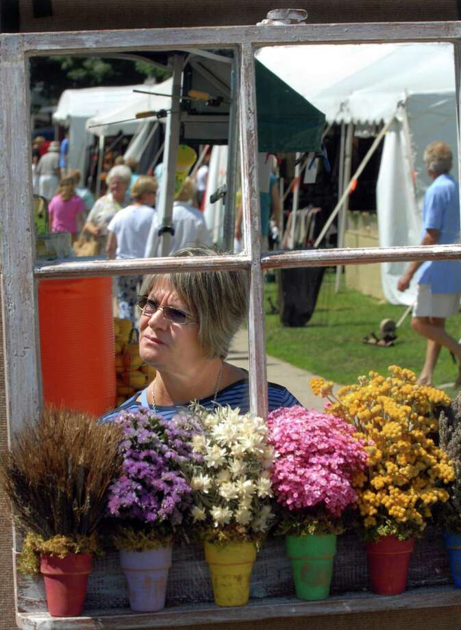 In this file photo, a woman is reflected in a mirrored, floral, shadow box at a Guilford Art Center Craft Expo on the Guilford Green. The center is is one of the winners in the 2019 New Haven Register Reader's Choice poll Best Place to Purchase Art category. Photo: Hearst Connecticut Media File Photo /