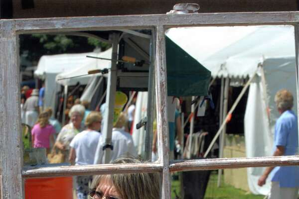 In this file photo, a woman is reflected in a mirrored, floral, shadow box at a Guilford Art Center Craft Expo on the Guilford Green. The center is is one of the winners in the 2019 New Haven Register Reader's Choice poll Best Place to Purchase Art category.