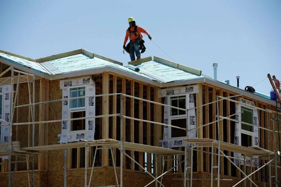 In this April 13, 2015, photo, a worker helps to build a new home at a housing tract in Las Vegas. The number of new housing permits issued in Connecticut last month was down by 33.4 percent compared to February 2018. Photo: John Locher / Associated Press File / AP