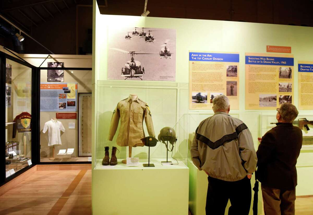 Vietnam veterans, Roy McDonald of Troy, left, and John Sacca of Clifton Park, right, examine one of the displays they're featured in on a new Vietnam and Korean War exhibit at the New York State Military Museum on Friday, March 29, 2019, in Saratoga Springs, N.Y. McDonald served as a forward observer in the 9th Cavalry and Sacca was a door gunner and radio operator in the 1st Cavalry Division. March 29 is Vietnam Veterans Day, marking March 29, 1973, when the last combat soldier left Vietnam. (Will Waldron/Times Union)
