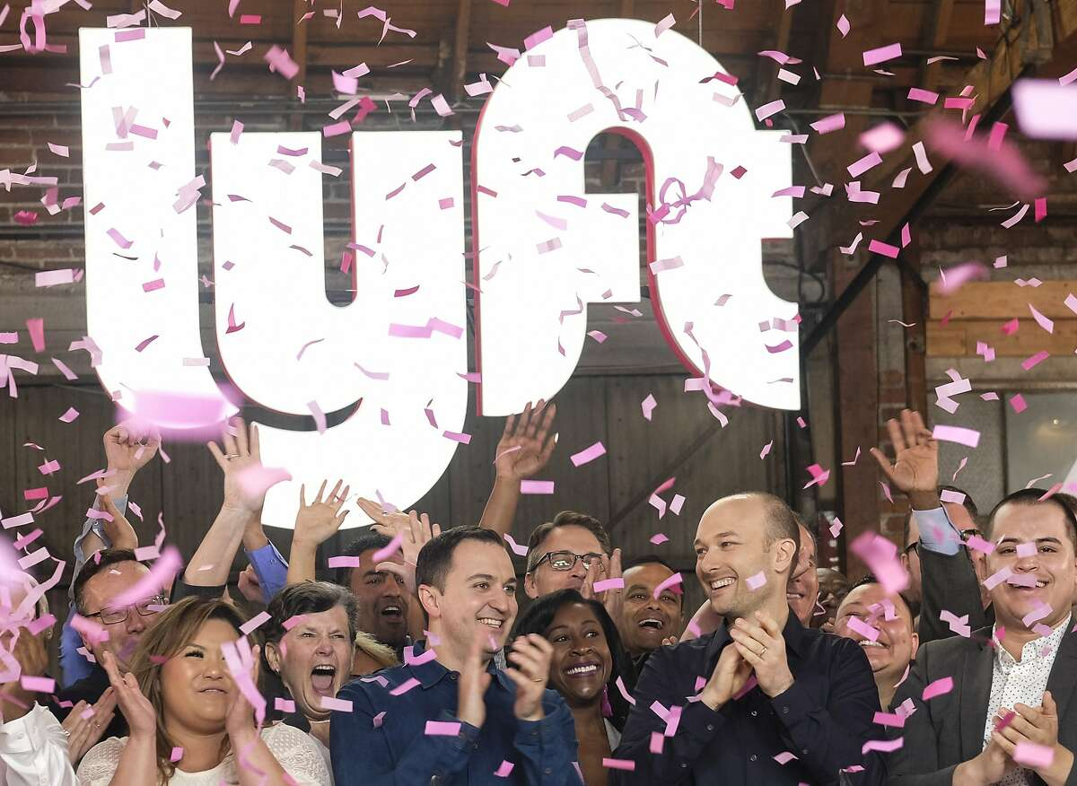 Lyft co-founders John Zimmer, left, and Logan Green cheer as they ring a ceremonial opening bell in Los Angeles, Friday, March 29, 2019. On Friday the San Francisco company's stock began trading on the Nasdaq exchange under the ticker symbol