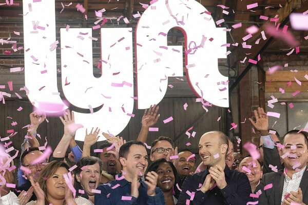 """Lyft co-founders John Zimmer, left, and Logan Green cheer as they ring a ceremonial opening bell in Los Angeles, Friday, March 29, 2019. On Friday the San Francisco company's stock will begin trading on the Nasdaq exchange under the ticker symbol """"LYFT."""" (AP Photo/Ringo H.W. Chiu)"""