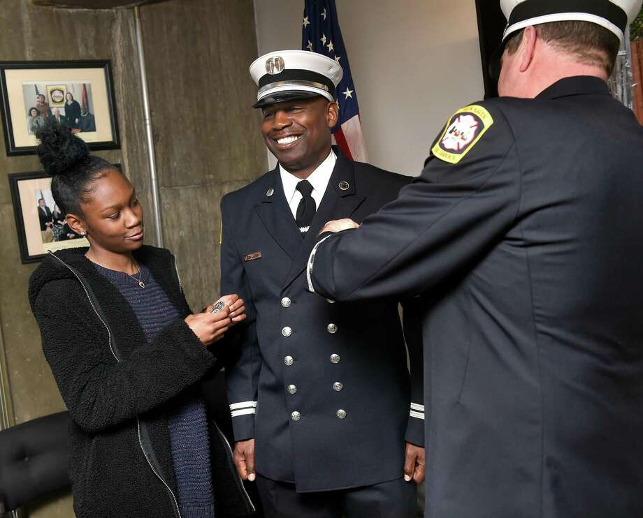 New Haven Fire Department Capt. Gerard Bellamy, center, has his new badge put on by his daughter, Taryn, and retired Capt. James Bohan during a promotion ceremony at  New Haven Fire Department headquarters March 29, 2019. Photo: Arnold Gold / Hearst Connecticut Media / New Haven Register