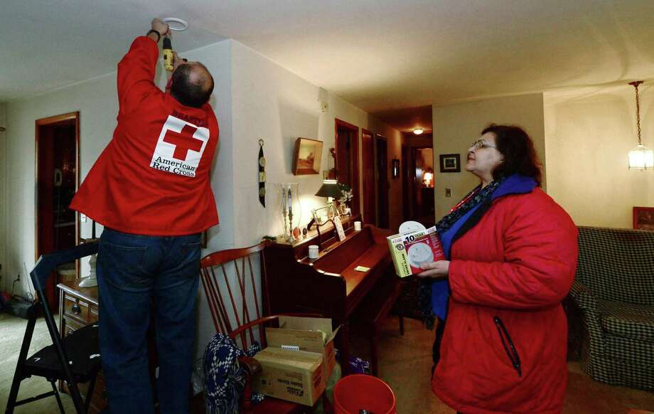 Red Cross of Rhode Island and Connecticut CEO Mario Bruno and volunteer Amira Mantoura replace smoke detectors in the home of Norwalk resident Elaine Andersen in 2017. Photo: Erik Trautmann / Hearst Connecticut Media / Norwalk Hour