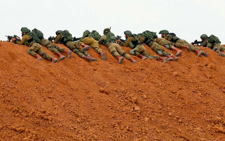(FILES) In this file photo taken on March 30, 2018 Israeli soldiers keep position as they lie prone over an earth barrier along the border with the Gaza Strip in the southern Israeli kibbutz of Nahal Oz as Palestinians demonstrate on the other side commemorating Land Day. - A year after the start of protests, labelled the Great March of Return,  and clashes on the Gaza-Israel border, more than 200 Palestinians have been killed by Israeli fire. More than 8,000 operations for other often serious but not life-threatening conditions -- such as gallstones or hip replacements -- have been postponed in Gaza hospitals according to the WHO. Explosive devices, stones and fireworks have been used against Israeli forces. There has been occasional gunfire, with one soldier killed by a Palestinian sniper. (Photo by Jack GUEZ / AFP)JACK GUEZ/AFP/Getty Images Photo: Jack Guez / AFP / Getty Images 2018