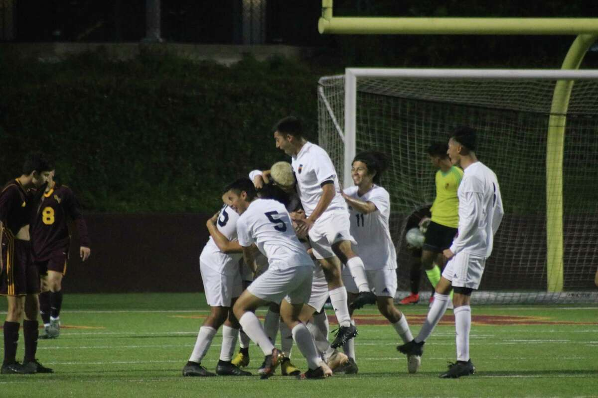 Memorial soccer players mob Oscar Aguirre after he kicked in a tying goal late in the first half of Thursday night's bi-district match with Deer Park.