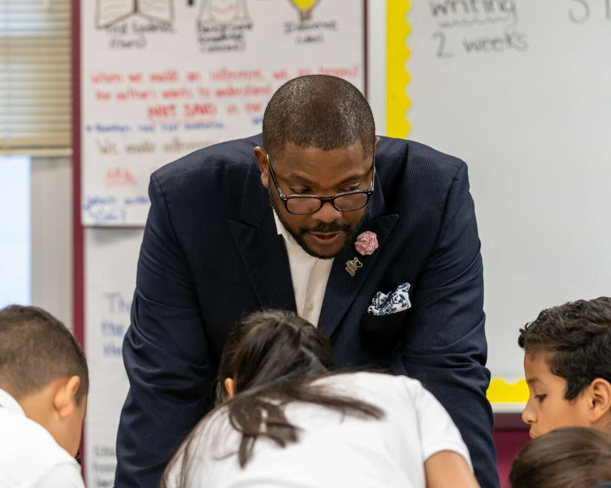 Superintendent Orlando Riddick works with students on their investigation into Texas history.