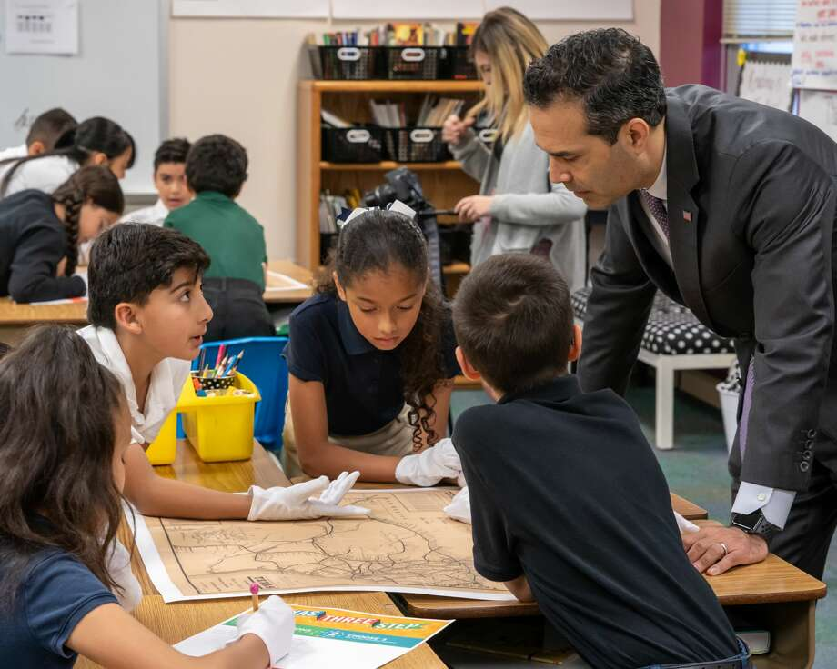 Texas Land Commissioner George P. Bush works with Milam students. Students wore white gloves just as archivists at the General Land Office do when handling artifacts such as maps. Photo: Midland ISD