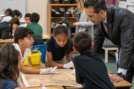 Texas Land Commissioner George P. Bush works with Milam students. Students wore white gloves just as archivists at the General Land Office do when handling artifacts such as maps.