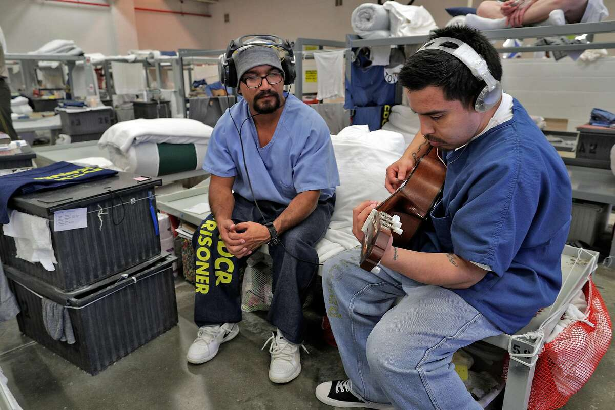 Miguel Katwaroo, left, teaches Robert Adame, right, how to play guitar in the education dormitory at the Central Valley Modified Community Correctional Facility in McFarland, Calif., on Thursday, March 28, 2019. California Gov. Gavin Newsom is trying to figure out how to empty privately run prisons of California inmates, who would be sent to state-run lockups like this one run by GEO Group.